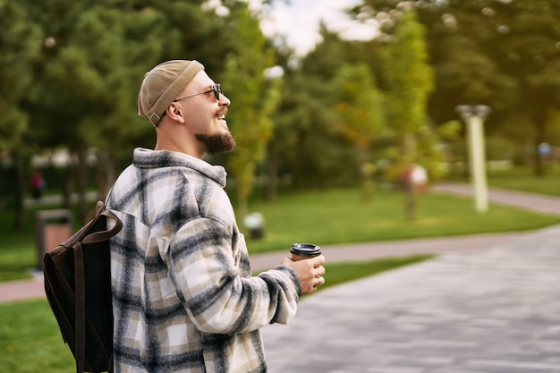 Side view of hipster bearded student looks sideways while walks in urban city park rest day