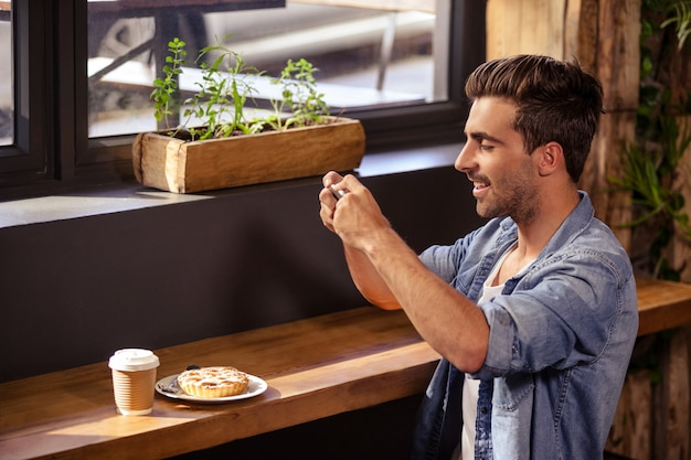 Side view of hipster man taking photo of his meal