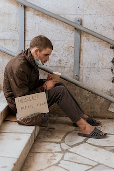 Vista laterale del senzatetto che tiene tazza e segno di aiuto
