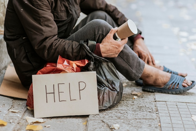 Side view of homeless man holding cup and help sign