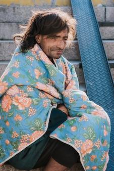 Vista laterale di un senzatetto all'aperto con coperta