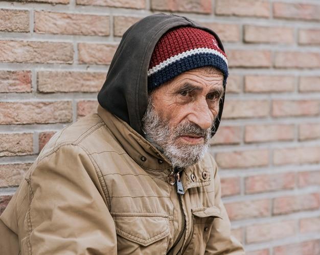 Vista laterale di un senzatetto all'esterno