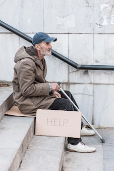 Side view of homeless man on stairs with cane and help sign