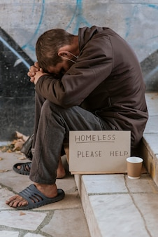 Side view of homeless man on stairs with cup and help sign