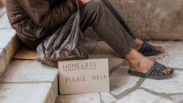 Vista laterale di un senzatetto sulle scale con segno di aiuto