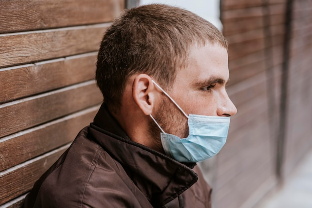 Side view of homeless man on the street with medical mask