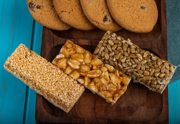 Side view of honey bars with peanuts sesame and sunflower seeds with oatmeal cookies on a wooden board