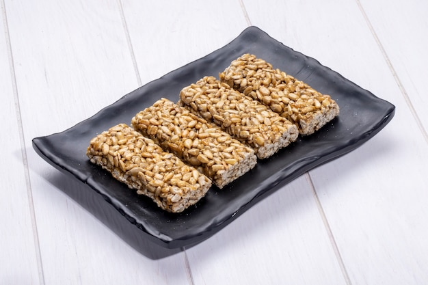 Side view of honey bars with sunflower seeds on a black platter on rustic