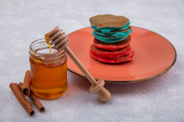 Side view honey in a jar with a wooden spoon  cinnamon and colorful pancakes on an orange plate on a white background