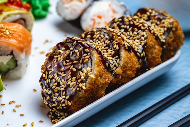 Side view hot roll deep fried sushi roll with teriyaki sauce and sesame seeds on a plate