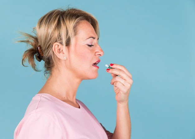 Side view of a ill woman taking vitamin capsule