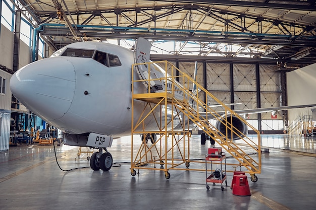 Side view image of big white passenger aircraft standing in the parking apron in the aviation hangar
