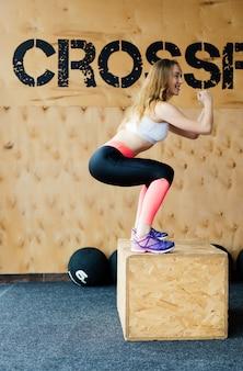 Immagine di vista laterale della giovane donna adatta che fa un esercizio di salto di scatola. donna muscolare che fa un box squat in palestra