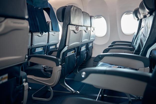 エコノミークラスの椅子に乗客がいない空の飛行機の座席と窓の側面図