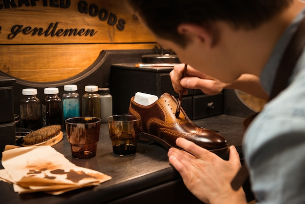 Side view image of young concentrated shoemaker