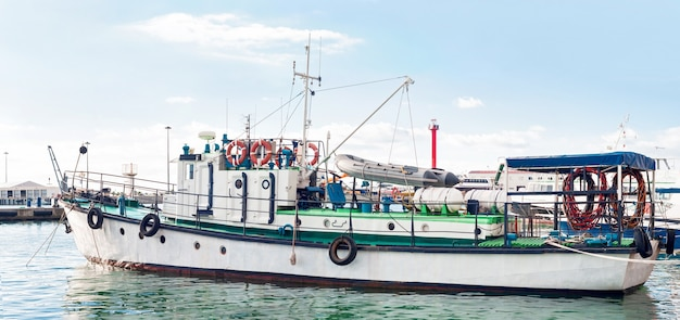 Side view of industrial boat for fishing, diving or tug service. motor cruiser with rubber boat anchored at sea port