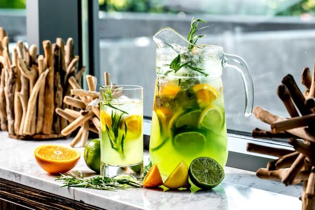 Вид сбоку бодрящий лимонад с лимоном лайм апельсин и эстрагон
