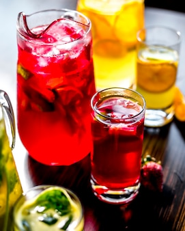 Side view invigorating variety soft drinks with a slice of lemon and strawberries on the table