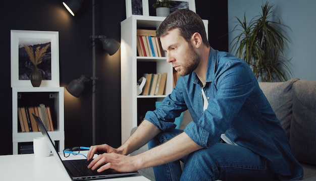 Side view of involved man using laptop sitting on sofa bent forward to coffee table staying home