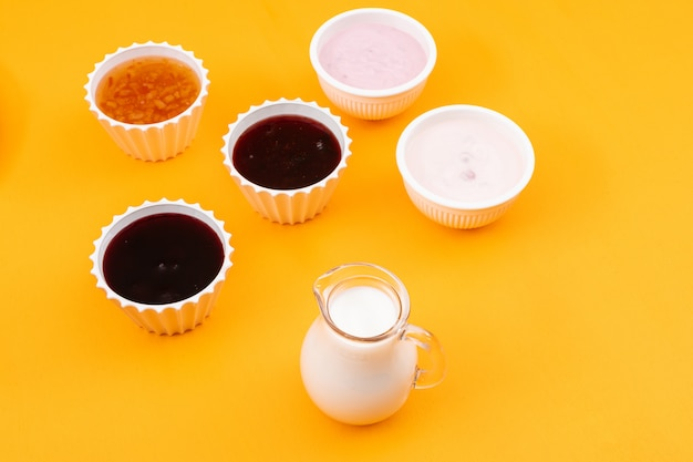 Side view of jam with milk and yogurt on yellow surface horizontal