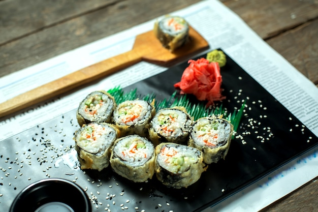 Side view of japanese traditional food tempura sushi maki served with ginger and soy sauce on black board