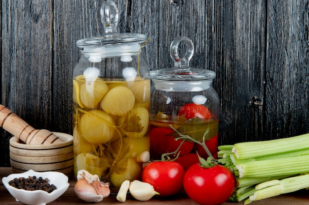 Side view of jars of pickled tomato with vegetables black pepper and garlic crusher on wooden background with copy space