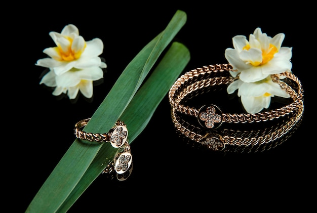 Side view of jewelry set of golden bracelet and ring with diamonds