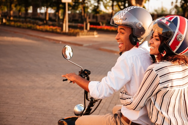 Side view of joyful african couple rides on modern motorbike in park