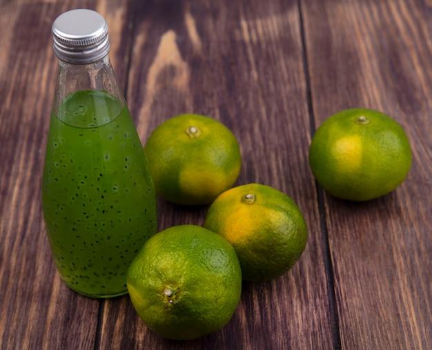 Bottiglia di succo di vista laterale con mandarini verdi sulla parete di legno