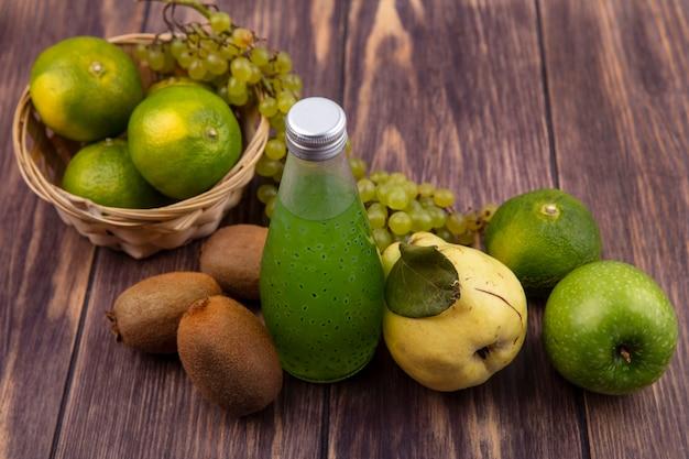 木製の壁のバスケットに梨キウイみかんリンゴとブドウの側面図ジュースボトル