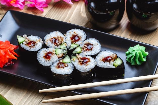 Side view kappa maki with fried fish cucumber teriyaki sauce wasabi and ginger on a board