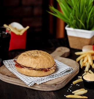 Vista laterale del doner di kebab con carne di manzo e verdure nel pane sul tagliere di legno