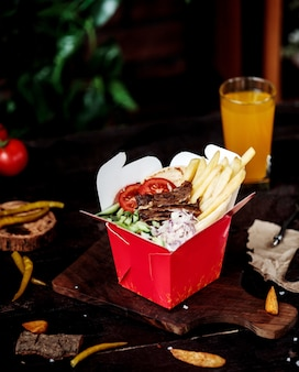 Side view of kebab meat with vegetable salad and french fries in cardboard bag on wooden cutting board