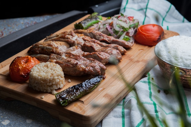 Side view kebab ribs with fried vegetables and chopped onion and ayran and knife in cutting board