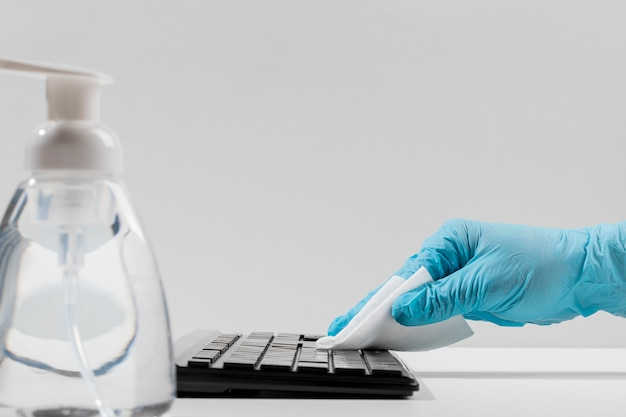 Side view of keyboard being disinfected by hand with surgical glove