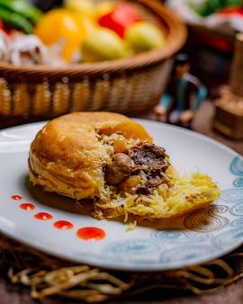 Вид сбоку хан плов с шафрановым рисом, завернутым в насыщенный маслом лаваш с говядиной, изюмом, изюмом и курагой