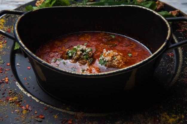 Вид сбоку харчо со специями и зеленью в темной тарелке