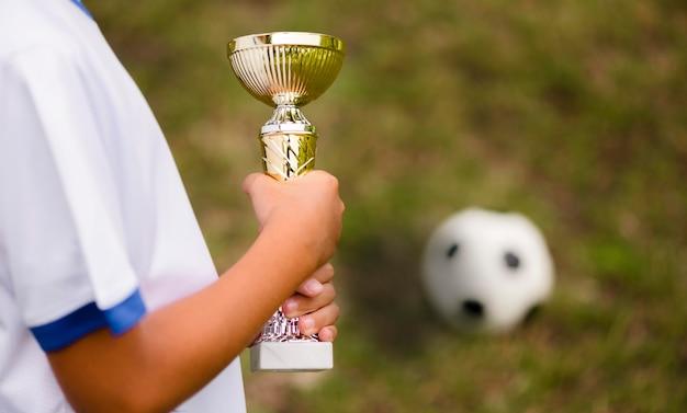 Вид сбоку ребенок побеждает после футбольного матча