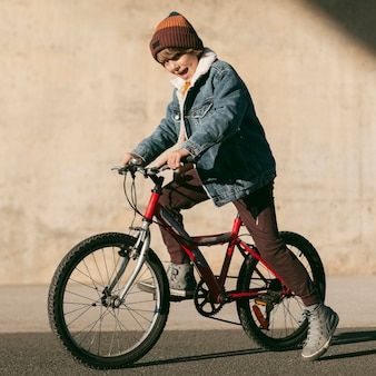 Side view of kid on bike outdoors having fun