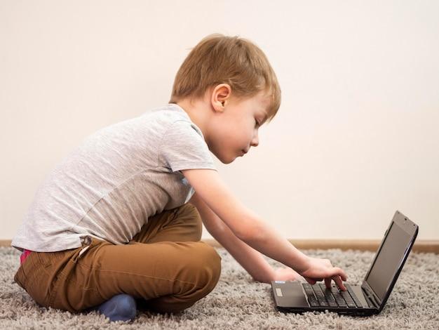 Вид сбоку ребенок играет на ноутбуке