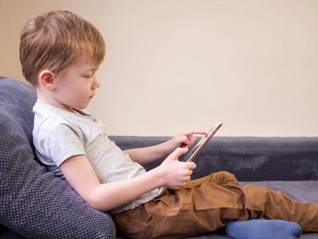 Вид сбоку малыш играет на планшете