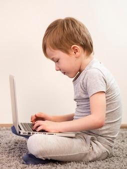 Вид сбоку малыш играет на полу со своим ноутбуком