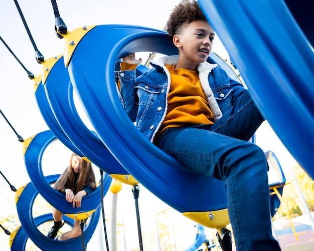 Вид сбоку дети веселятся на детской площадке