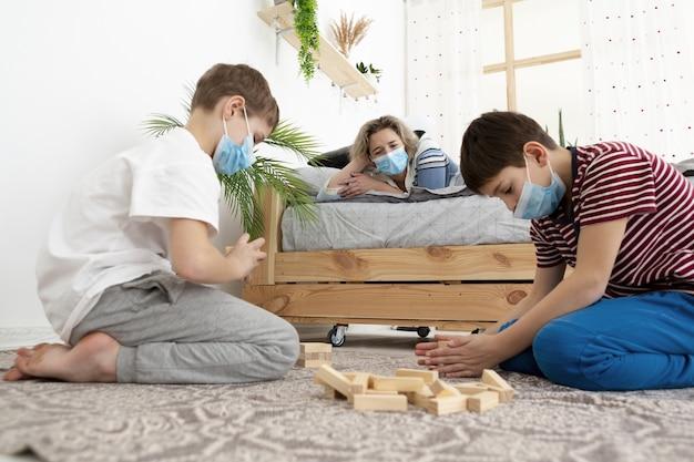 Vista laterale dei bambini a casa indossando maschere mediche e giocando jenga