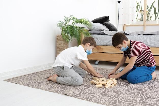Vista laterale dei bambini che giocano a jenga a casa mentre indossano maschere mediche