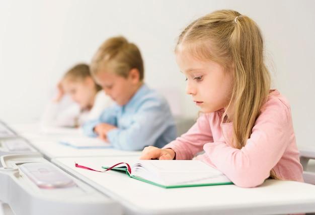 Bambini di vista laterale che leggono la loro lezione