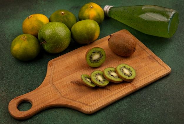 감귤 커팅 보드에 측면보기 키위 조각과 녹색 벽에 주스 한 병