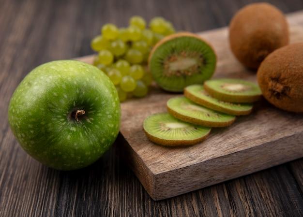 木製の背景に青リンゴとスタンドに緑のブドウと側面図キウイスライス