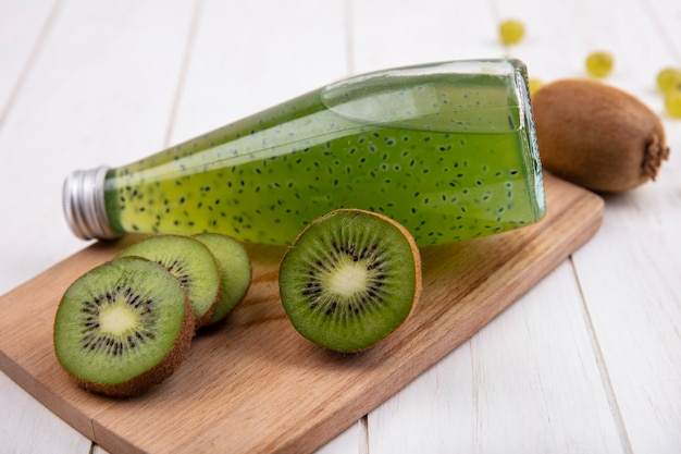 Side view kiwi wedges with a bottle of juice on a cutting board on a white wall