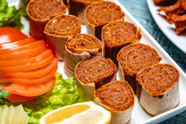 Вид сбоку рулет lahmacun с нарезанными листьями салата помидорами и ломтиком лимона на тарелке